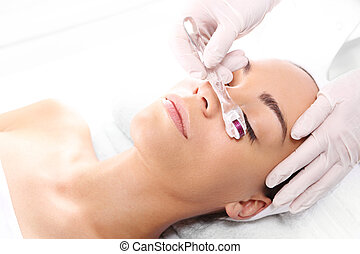 Roller microneedle mesotherapy - Beautician performs a...