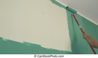 Roller painting wall with aquamarine paint