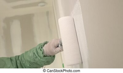 Roller painting white wall, ceiling with white paint