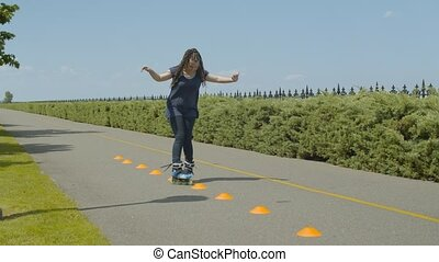 Skillful female skater making inline slalom stunts of bypass cones rollerblading along park alley. Positive woman with long ponytail from afro-braids inline skating crisscross course on footpath.