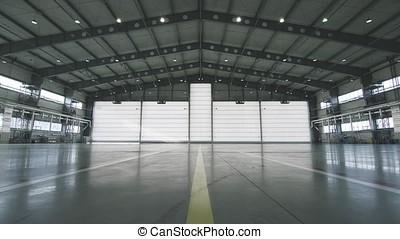 Roller shutter door and concrete floor inside factory building for industrial background. Airplane in front of half opened door to hangar. The open door of the hangar. Mechanic opening the door