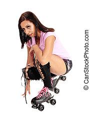 Roller skating woman crouching on floor