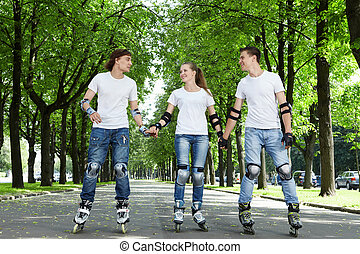 Three young people riding on roller skates holding hands