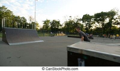 Rollerskater does various tricks in skate park -...