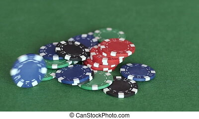 Rolling casino chips on pile in middle of the table