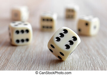 Rolling dice on a wooden desk.