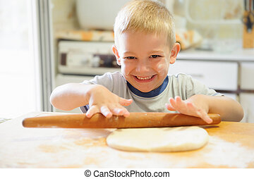 Little boy rolling dough in the kitchen