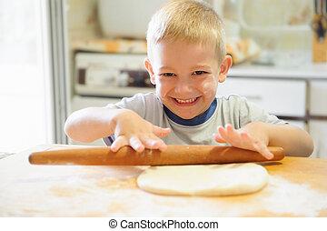 Rolling dough - Little boy rolling dough in the kitchen