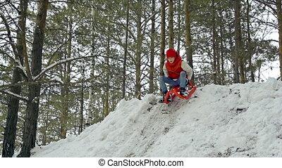Rolling Downhill - Boy riding toboggan down the hill