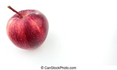 Rolling fresh apple on white background