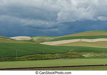 Rolling green farm fields with angry storm - Rolling green...