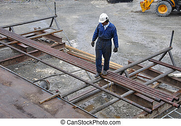 rolling out pipes - Drilling crewman selects pipes for...