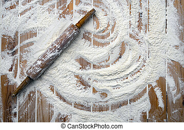 Rolling pin with flour on wooden table, baking background, top view, copy space for your text