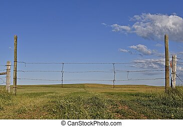 Barren hilly prairie pasture ranch land lies beyond a wire gate