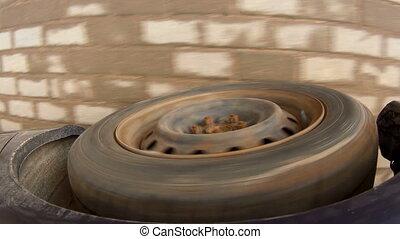 Rolling rubber tire of dark blue car on the asphalt road.