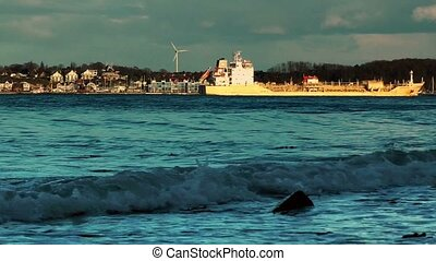 Rolling waves and cargo ship on coastline of Laboe, Kiel,...