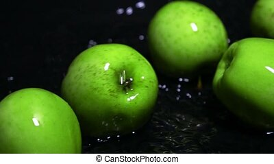 Rolling wet green apples and water ripple super slow motion...