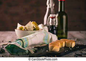 Rolls from smoked cheese on dark wooden board with few glasses in background