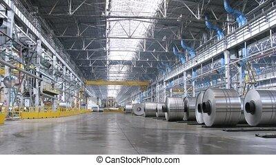 Rolls of aluminum lie on floor in production workshop of...