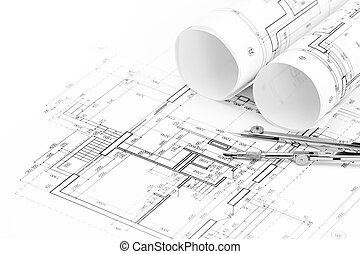 rolls of architectural blueprints and floor plan with drawing compass