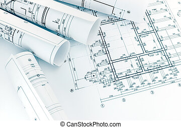 rolls of architecture blueprints with floor plan drawing on architects workspace