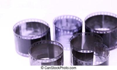 Rolls of black and white negative film revolve on light surface