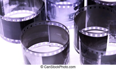 Rolls of black and white negative film revolve on light surface