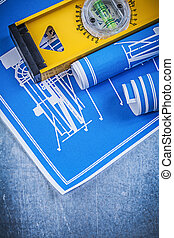 Rolls of blue engineering drawings level on metallic background