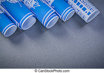 Rolls of blue engineering drawings on grey background constructi
