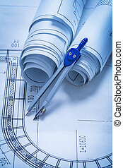 Rolls of blueprints and drawing compass construction concept
