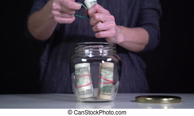 Rolls of dollars are put in a glass jar and closed with a metal lid