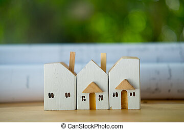 Rolls of residential home blueprints and miniature home