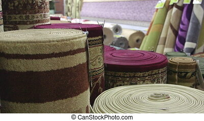 Rolls of rugs and carpets in flooring store staff serving customers