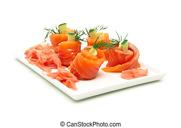Rolls of salmon with cucumber and dill on a plate.