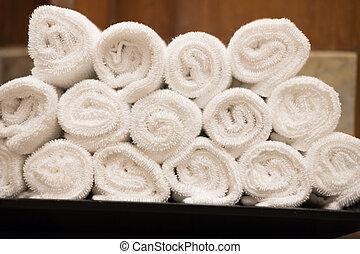 Rolls of white cotton towel in bedroom.