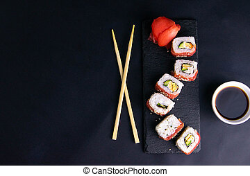 Rolls on a granite stand for sushi are laid out in the form of a dragon, next to stand sticks for sushi and soy sauce.