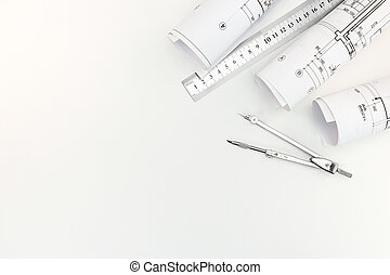 rolls with architectural plans and schemes with drawing compass and metal ruler on white background
