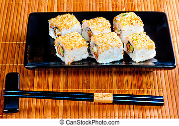 rolls with eel and sesame seeds on a beautiful dish