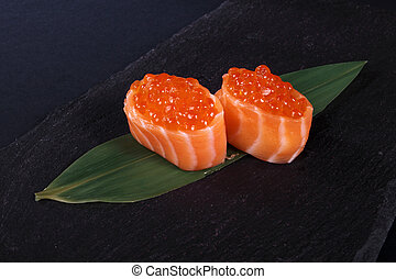 rolls with fish eggs on leaf green, black background