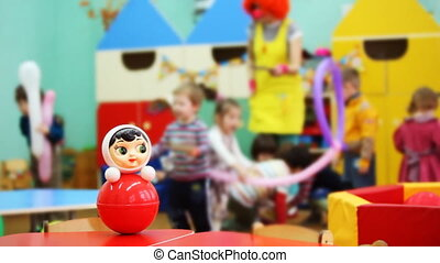 roly-poly toy on table, then focus moved to children playing with clown in kindergarten