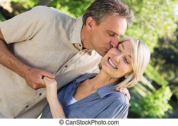 romántico, hombre, besar, mujer, en el estacionamiento