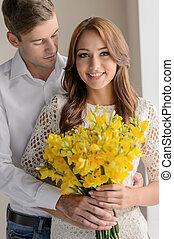 romántico, moment., retrato, de, hermoso, pareja joven, posición, mientras, valor en cartera de mujer, un, ramo de la flor