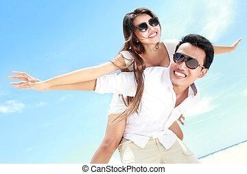 romántico, pareja joven, en la playa, tener diversión
