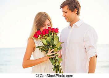 romántico, pareja joven, enamorado, hombre, dar, hermoso, mujer joven, rosas rojas