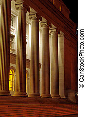 Roman columns at night - A row of tall roman columns at...