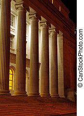 Roman columns at night - A row of tall roman columns at...