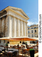 Roman temple Maison Carree and outdoor cafe in city of Nimes in southern France
