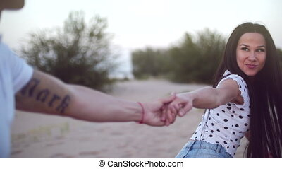 Romance Concept, Young Couple, Holding hands run on sand barefoot, woman holding the hand of her lover, runs ahead, looking him in the eye.