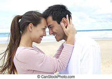 romance on vacation: couple in love on the beach flirting