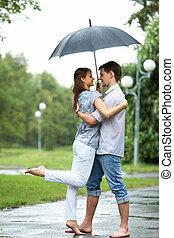 Romance - Portrait of woman and man embracing under umbrella...